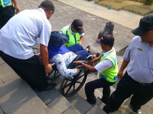 3 workshop participants carrying a wheelchair user up some stairs